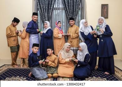 Kota Bharu,Malaysia-June 15th,2018 : Group of Asian family wearing Malay traditional clothing gathering during Eid al-Fitr celebration . Family , Happiness and Forgiveness Concept.