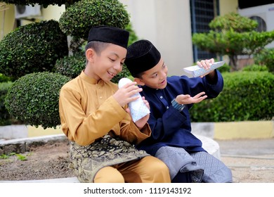 Kota Bharu,Malaysia-June 16th,2018 :The Malay boys wearing Malay traditional cloth or Baju Melayu showing their happiness reaction after received money pocket during Eid Fitri or Hari Raya celebration
