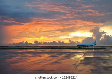 Kota Kinabalu (Borneo, Malaysia) airport in dramatic sunset light. Airplane ready to take off. Sunset sky reflection in wet runway after storm.