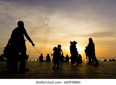 KOTA KINABALU, MALAYSIA - FEBRUARY 11, 2017: Silhouettes of an adult playing bubble with children in Tanjung Aru beach, Sabah Borneo.
