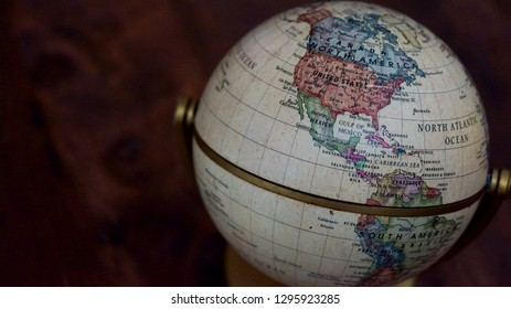 Kota Kinabalu, Malaysia - Jan 26, 2019; Close up shot of vintage globe model with a map of the world over wooden table as background. Selected focus.