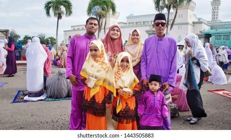 "Kota Kinabalu, Malaysia, June 05, 2019: Malay family wearing traditional cloths call ""Baju Melayu"" and ""Baju Kurung"" at the the mosque after Aidilfitri prayed."