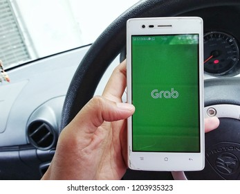 Kota Kinabalu, Malaysia,October 13, 2018 : A woman is using Grab application on smartphone. Grab is a Malaysian technology company that offers ride-hailing and logistics services through its app.