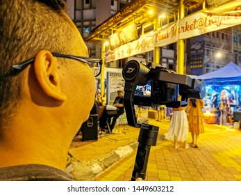 Kota Kinabalu, Sabah, 12 July 2019: Behind the scene of a night market shooting. A videographer using his camera and gimbal for night video