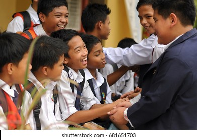 Kota Kinabalu, Sabah. August 2, 2013: A group of students greeting each other at a school compound. Malaysian schools aim to create no bullying environment for students through awareness and education
