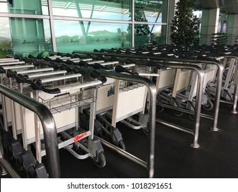 Kota Kinabalu, Sabah - January 10, 2018: Hand holding luggage trolleys in Kota Kinabalu International Airport.