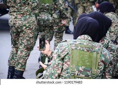 Kota Kinabalu, Sabah, Malaysia : Aug 31, 2018 : Two women wearing army uniforms taking photos together. Malaysia celebrate independence day on the month of August.