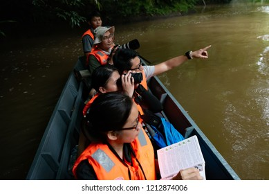 Kota Kinabalu Sabah Malaysia - August 9, 2018 : A group of bird watchers exploring into the depth of tropical jungles. And a young woman with binoculars.