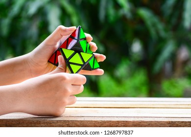 Kota Kinabalu Sabah Malaysia - Dec 21, 2018: A triangle Rubik's Cube with nature  green background. The teaching of thinking skills in classroom may be included in the curriculum in a variety of ways.