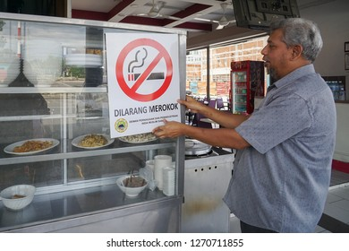 Kota Kinabalu Sabah Malaysia - Dec 31, 2018 : Restaurant operator holding a No Smoking signage. Malaysia to enforce law that all eatery in Malaysia is Non Smoking Area start on Jan 1, 2019.