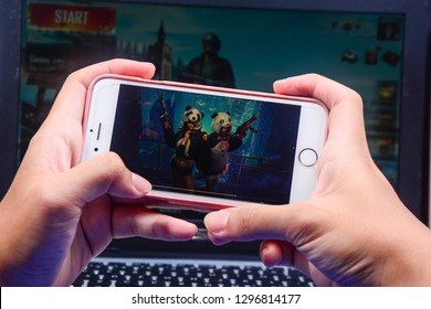 Kota Kinabalu Sabah, Malaysia - Jan 23, 2019: A hand holding a smartphone playing PUBG games online. Iphone's screen shows two girls in special suits. Multimedia games are famous among students.