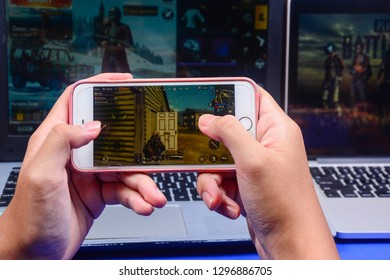 Kota Kinabalu Sabah, Malaysia - Jan 23, 2019: A hand holding a smartphone playing PUBG games online. Screen shows player looting for weapon and supplies. Multimedia games are famous among students.