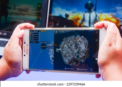 Kota Kinabalu Sabah, Malaysia - Jan 23, 2019: A hand holding a smartphone playing PUBG games online. Screen shows a Vikendi map. Multimedia games are famous among students.