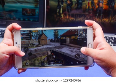 Kota Kinabalu Sabah, Malaysia - Jan 23, 2019: A hand holding a smartphone playing PUBG games online. Screen shows a player looting for weapon and supplies. Multimedia games are famous among students.