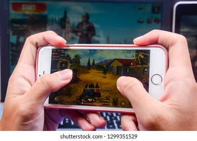 Kota Kinabalu Sabah, Malaysia - Jan 23, 2019: A hand holding a smartphone playing PUBG games online. Screen shows player kills an enemy. Multimedia games are famous among students.