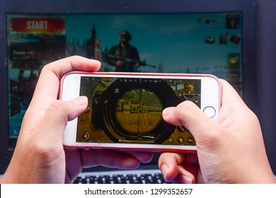 Kota Kinabalu Sabah, Malaysia - Jan 23, 2019: A hand holding a smartphone playing PUBG games online. Screen shows player shooting using scope in training session.
