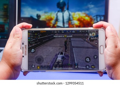 Kota Kinabalu Sabah, Malaysia - Jan 23, 2019: A hand holding a smartphone playing PUBG games online. Screen shows player waiting for airplane boarding. Multimedia games are famous among students.
