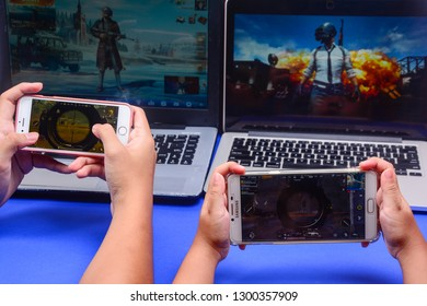 Kota Kinabalu Sabah, Malaysia - Jan 23, 2019: Two set of hands playing PUBG games multiplayer online using laptop and smartphones.  Games technology should be use in education to attract students.
