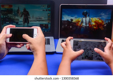 Kota Kinabalu Sabah, Malaysia - Jan 23, 2019: Two set of hands playing PUBG games multiplayer online using laptop and smartphones.  Games technology should be use in education to attract student.