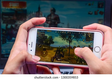 Kota Kinabalu Sabah, Malaysia - Jan 23, 2019: A hand holding a smartphone playing PUBG games online. Screen shows player running through a battlefield. Multimedia games are famous among students.