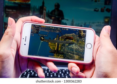 Kota Kinabalu Sabah, Malaysia - Jan 23, 2019: A hand holding a smartphone playing PUBG games online. Screen shows an airplane flying across Erangel island. Multimedia games are famous among students.