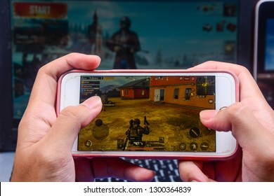 Kota Kinabalu Sabah, Malaysia - Jan 23, 2019: A hand holding a smartphone playing PUBG games online. Screen shows player looking for supplies among houses. Multimedia games are famous among students.