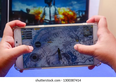 Kota Kinabalu Sabah, Malaysia - Jan 23, 2019: A hand holding a smartphone playing PUBG games online. Screen shows player jumping off from an airplane. Multimedia games are famous among students.