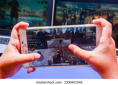 Kota Kinabalu Sabah, Malaysia - Jan 23, 2019: A hand holding a smartphone playing PUBG games online. Screen shows squad players moving together. Multimedia games are famous among students.