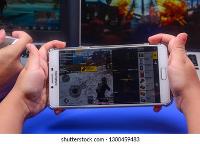 Kota Kinabalu Sabah, Malaysia - Jan 23, 2019: A hand holding a smartphone playing PUBG games online. Screen shows player checking items inside backpack. Multimedia games are famous among students.