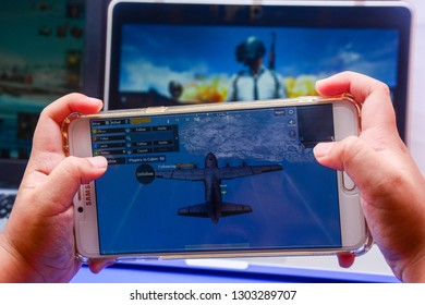 Kota Kinabalu Sabah, Malaysia - Jan 23, 2019: A hand holding a smartphone playing PUBG games online. Screen shows a plane flying over Vikendi Island. Multimedia games are famous among students.