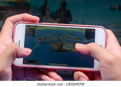 Kota Kinabalu Sabah, Malaysia - Jan 23, 2019: A hand holding a smartphone playing PUBG games online. Screen shows an airplane flying over Erangel island. Multimedia games are famous among students.