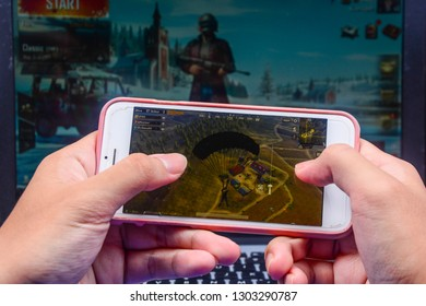 Kota Kinabalu Sabah, Malaysia - Jan 23, 2019: A hand holding a smartphone playing PUBG games online. Screen shows player jumping off plane using parachutes. Multimedia games are famous among students.