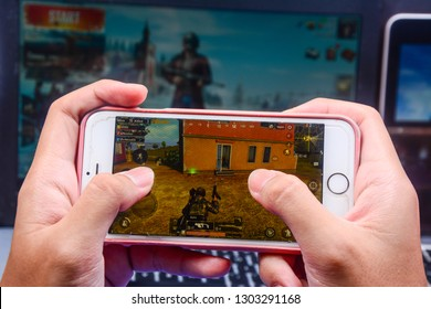 Kota Kinabalu Sabah, Malaysia - Jan 23, 2019: A hand holding a smartphone playing PUBG games online. Screen shows a player killing an enemy. Multimedia games are famous among students.