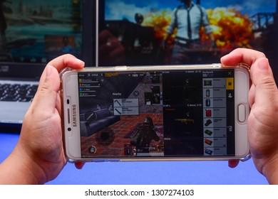 Kota Kinabalu Sabah, Malaysia - Jan 23, 2019: A hand holding a smartphone playing PUBG games online. Screen shows player checking items inside his backpack. Multimedia games are famous among students.