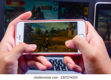 Kota Kinabalu Sabah, Malaysia - Jan 23, 2019: A hand holding a smartphone playing PUBG games online. Screen shows player running through battlefield. Multimedia games are famous among students.