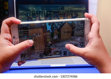 Kota Kinabalu Sabah, Malaysia - Jan 23, 2019: A hand holding a smartphone playing PUBG games online. Screen shows players shooting an enemy. Multimedia games are famous among students.