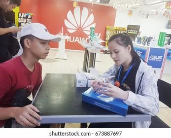 Kota Kinabalu Sabah, Malaysia - July 9, 2017: Young teenage and salesperson at mobile shop in Kota Kinabalu with Vivo and huawei logo visible.