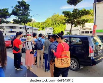 Kota Kinabalu Sabah, Malaysia - June 27, 2017: Tourist waiting for taxi in front of Suria Mall KK.