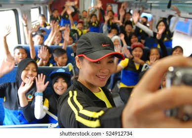 Kota Kinabalu, Sabah, Malaysia. March 7, 2015: A teacher taking a 'selfie' while cheperoning a group of happy looking school children for a train ride as school extracurricular activity.