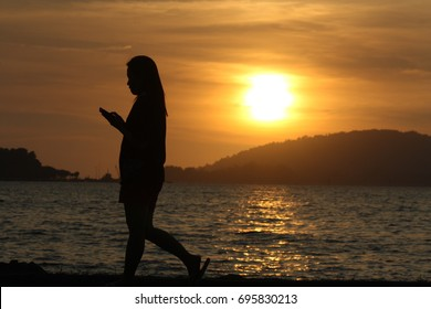 Kota Kinabalu Sabah, Malaysia - March 3, 2014 - Silhouette of people holding phone during sunset at Tanjung Lipat Beach.KK is known as the best place to see beautiful sunset in the world.