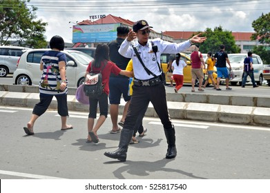 Kota Kinabalu, Sabah, Malaysia. May 31, 2016: A Traffic police officer assisting some pedesterian passing a busy road. Traffic officer in Malaysia is under the Malaysian Royal Police department.