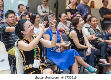 Kota Kinabalu, Sabah , Malaysia - May 22, 2017 : A lady in Traditional costume with holding hand phone with capture some pic