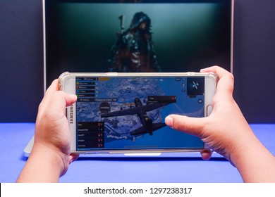 Kota Kinabalu Sabah, Malaysia-Jan 23, 2019: A hand holding a smartphone playing PUBG games online. Screen shows an airplane carrying players to battlefield. Multimedia games are famous among students.