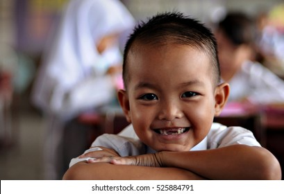 Kota Kinabalu, Sabah. May 3, 2012: 7 years old primary school boy smiles in his classroom in a Malaysian primary school. Early childhood education is cumpulsory for every children in Malaysia.