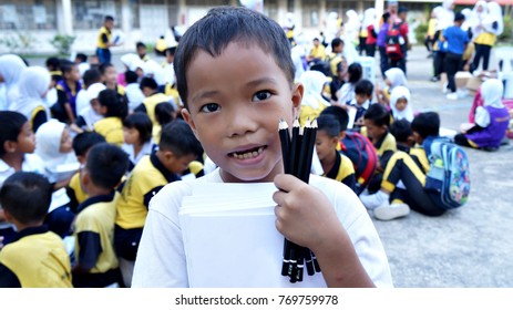 Kota Kinabalu, Sabah. November 11, 2017: Primary school boy showing stationary supplied by the state government. Sabah State Government provide social aid program for primary school students everyear