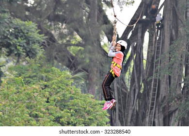 Kota Kinabalu, Sabah. September 30, 2015 : A young girl propelling on a flying fox at Outward Bound School Kinarut, Sabah. Flying fox is a small scale zip line that enable user to propell by gravity.