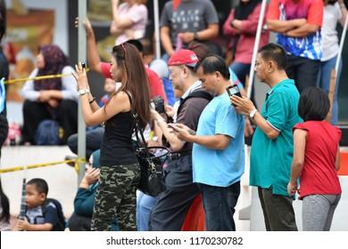 Kota Kinabalu, Sabah-Aug 31, 2018: Unidentified people holding smartphone during National Day celebration.