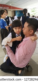 Kota Kinabalu, Sabah-Jan 2,2019: A child experiencing separation anxiety clings to her father during first day of school.