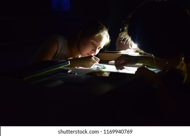 Kota Kinabalu, Sabah-Sept 2,2018:Two young women continue working on a project in the dark at night after power failure. They use the light emitted by their hand phones as light source.