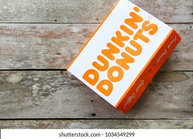 KOTA KINABALU,SABAH,MALAYSIA. FEBRUARY 2018. Dunkin' Donuts is an American global donut company and famous branding fast food. Donut packaging on wooden table.